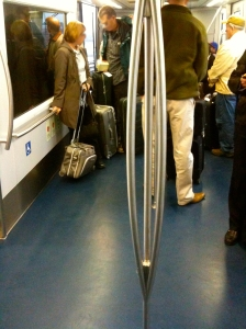 A pole to hang on to in the subway of the Atlanta airport. It divides into three poles to make more room to hold.